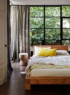 I love that this room is white, metal & wood, but looks warm and colorful from foliage beyond the windows & the colorful bedding--elements that can/will change throughout the year to keep the space new and interesting.