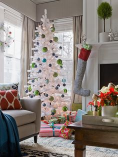 Tall, slim white christmas tree with blue and green ornaments. Love the difference in the scale of the ornaments..