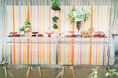 cake table with a streamer backdrop, photo by Troy Grover Photographers http://ruffledblog.com/colorful-wedding-at-hotel-ballard #weddingideas #caketables