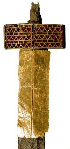 """Empuñadura de la spatha de Altlussheim (distr. Rhin-Neckar, Bade-Wurtemberg, Alemania). Mediados del siglo V. Guarda ancha, de tipo """"asiático"""", de bronce decorada en la parte delantera con un aplique de oro con decoración polícroma cloisonée (tabicada) de granates. Vian recubierta de chapa de oro. Karlsruhe, Badische Landesmuseum. Inv. nº C 11401 a-e."""