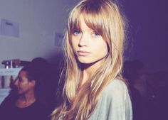 cut as full bangs that are blended down into layers around face and worn split off center