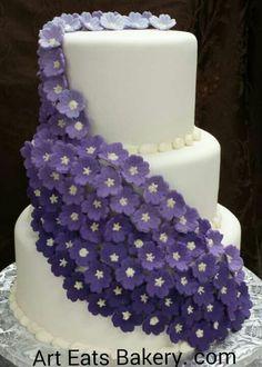 Three tier elegant modern white fondant wedding cake design with ombre purple edible flowers