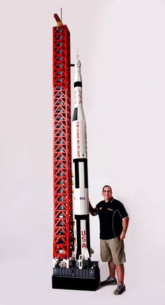 """LEGO Designer Ryan McNaught poses with his impressive large Saturn V rocket"""