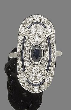 A sapphire and diamond plaque ring, circa 1930.  Of geometric design, centrally-set with an oval-cut sapphire, within a cushion-shaped and rose and single-cut diamond surround, highlighted with a row of calibré-cut sapphires, in millegrain-settings, diamonds approx. 1.00ct total