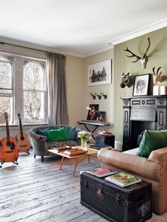rustic floors, leather couch, antlers, guitars, green pillows, black mantel, sheer linen drapes
