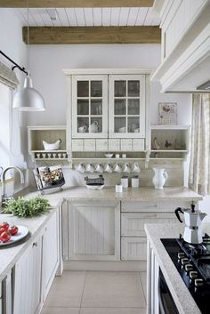 Small country-white kitchen -- Like the glass door top cabinet, chicken in a box, white board ceiling with dark beams...