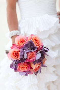 Vibrant, cheerful, lush coral pink and purple hued bridal bouquet.