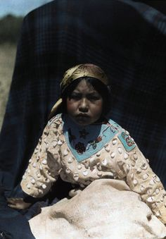 Montana - A Crow Indian child wears a buckskin dress of beads and teeth, Crow Indian Reservation