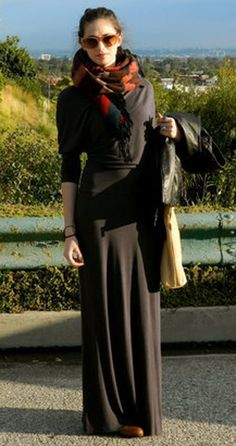 Long black maxi skirt with a comfy black crew neck sweatshirt and a black leather jacket. To give the simple monochromatic outfit a dash of color: light brown sunglasses, a gold tote, and a chunky multicolor scarf.