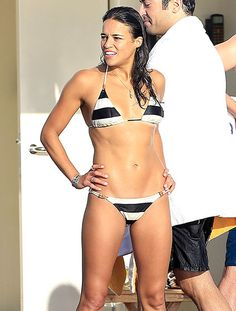 Ab alert! Michelle Rodriguez showed off her impressive abs in a striped bikini in Ibiza, Spain.