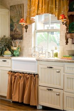 A French Provence Kitchen with a Franke farmhouse sink and two Fisher and Paykel dishwashers drawers. Limestone Versai patterned tile finished with vintage wall mounted sconces create an inviting kitchen.