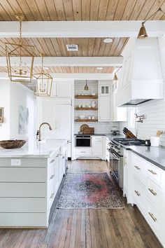 A red and black vintage rug sits on a thin plank floor accenting an expansive white kitchen.