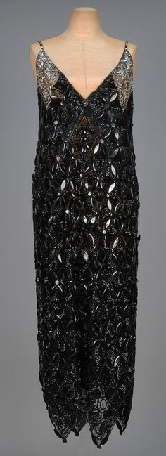 SEQUINED TULLE EVENING TABARD with RHINESTONES, circa 1923. Sleeveless black V-neck with an allover lattice of black paillettes on a black sequined ground, the shoulder decorated in marquise and round rhinestones with silver sequins, jeweled narrow strap, four large hem points having faceted paillettes and beads. FAMSF.