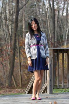 A pink belt over a dress and blazer