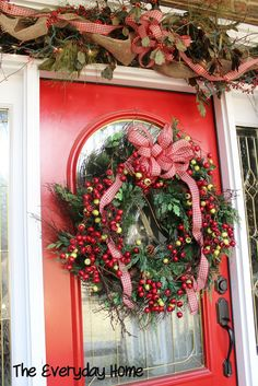 Southern Porch and a Red Door with a Berry festooned wreath via The Everyday Home