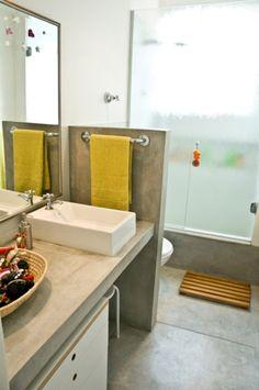 O piso e o rodapé de 40 cm são de cimento queimado, como a bancada e a parede que separa o espaço da bacia.