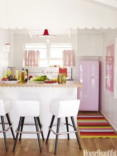 """Designer Krista Ewart used scalloped shapes throughout a Balboa Island beach house — such as in the kitchen island's trim and lighting. """"That was a total theme,"""" she says. """"Scallops are feminine, but not overly feminine, a great old-fashioned smiley shape. They're young and happy — like polka dots."""" The pink Smeg refrigerator from Sears is the showstopper in the guest-suite kitchen. Lina rug from Plastica. pink fridg, colors, beach houses, small kitchens, pink kitchens, cottages, scallop, cottage kitchens, kitchen designs"""