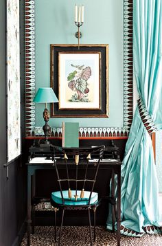 Luxe workspace with aqua silk curtains and framed art.