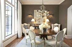 dining rooms - chic elegant French white leather Louis dining chairs walnut round dining table white curtains brown silk ribbon trim white wingback chairs Restoration Hardware glass column lamps brown purple pillows