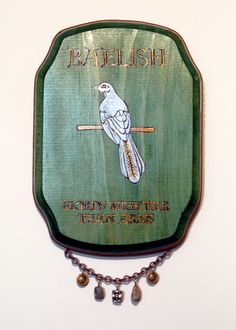 House Baelish sigil plaque commissioned piece from Ruth Fabiano. If you notice the charms, there are 2 coins representing his wealth, 2 stones representing the Fingers and the face represents House Baelish's stone face sigil, which Petyr discarded when he adopted the silver mockingbird as his sigil. We made up the house words, as Baelish's words are never mentioned. Check out her other plaques and boxes at her Etsy Shop.