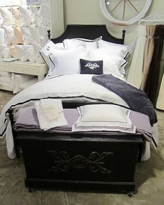 A stunning black metal bed compliments the chic white bedding with classic black trim from Downtown Company!