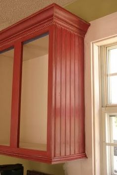 How to make builder grade oak cabinets look custom. Beadboard and a little extra molding make such a difference. Well then there is always the red paint too.