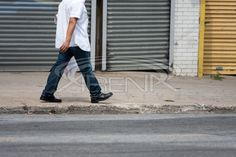Man Walking Along the Sidewalk Stock Photo #streetphotography #photography