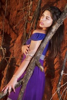View of a beautiful young girl with a purple dress standing on a red cliff on the beach. Stock Photo