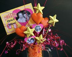 A mug, crinkle paper, sparkly objects, ribbon and a photo.  Perfect for a graduation centerpiece.