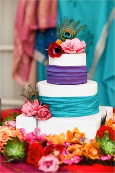 Purple and Teal Wedding Cake with an assortment of flowers and peacock feather.