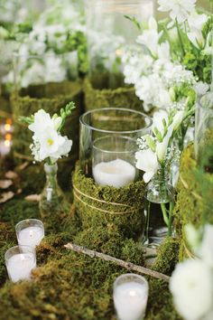 Table adornments of candles wrapped in moss and small flowers in bottles for an organic motif.  Photo by Kent Bristol Photography
