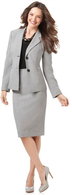 A suit with a knee-length skirt and a tailored blouse is most appropriate.