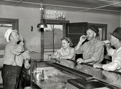"August 1937. ""A drink on the house. Lumberjacks, proprietor and lady attendant in saloon. Craigville, Minnesota."""