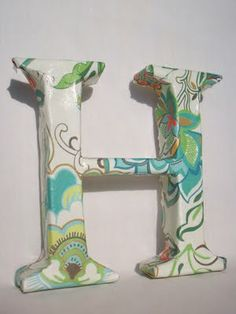 Cut a letter from styrofoam and modge podge decorative paper.
