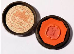 antique red wax seal with a Livery, Peerage symbol of a half dog or dogs head and neck holding a flower in its mouth. The wood box has the makers label under the lid, the name is LONGMAN STRONGI'TH'ARM 'Engravers to His Majesty, Waterloo Place, London'.