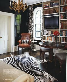 Zebra rug, gloss black walls, brown leather library. All the details.