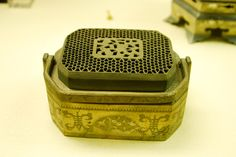 Qing Dynasty hand warmer, previously used during the winter months by placing hot coal in the brass handwarmer, displayed in the Forbidden City Palace collection.