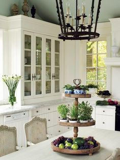 French country kitchen with white cabinetry and blue/green walls.  Iron pendant