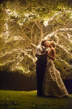 A kiss under a twinkle tree. I've always known I wanted an outdoor reception-- complete with this lighting in all the trees. It feels warm and ambient, the lighting like this. Perfect for my autumn wedding. :')