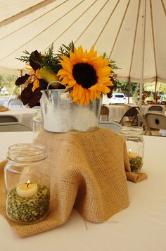 Autumn fall table centerpieces with split peas and tea lights in mason jars and sunflowers with greens from the backyard