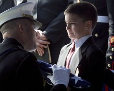 8 years old child crying when he received flag due to his father's death.