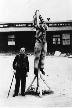 Buchenwald, Germany, 1945, A liberated prisoner demonstrating a style of punishment in the camp.
