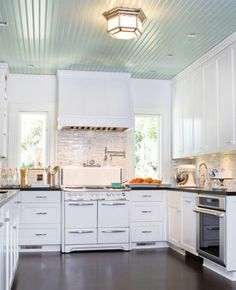 White kitchen with a quaint vintage stove and a beadboard ceiling in the most perfect blue imaginable.