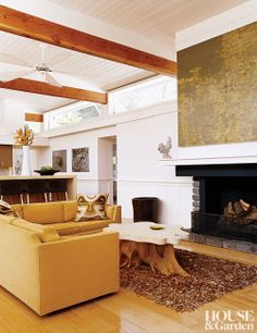 The warm family room of a northern California home has a gold L-shaped sofa and a rug made of leather remnants. #houseandgarden