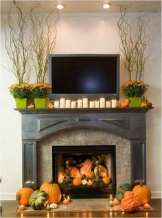 39 Amazing Fall Mantel Décor Ideas : Fall Mantel Décor With White Wall Black Fireplace Orange Pumpkin Fall Flower Ornament LED TV Hardwood Floor And Rug Design