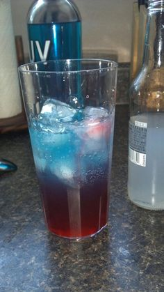 Bomb Pop drink: a bottle of Smirnoff Ice, a shot of UV Blue and a drizzle of grenadine