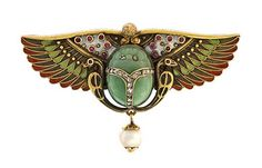 Egyptian revival scarab pin with brightly enameled horus wings.
