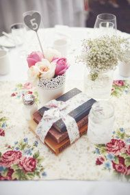 Whimsical wedding centerpiece. Lace on mason jars along with books and flowers.