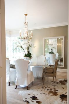 In the conservatory-style dining room, designer Angela Grady chose a shimmery liquid platinum wallpaper that changes shades in the light.