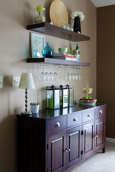 I like these floating shelves, the buffet and the wine glass holders.  It's a nice multi-purpose solution for a small space.
